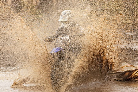 Motocross racer in a wet and muddy terrain in Parola, Finland. Water and mud splashing everywhere and covering the driver completely. photo