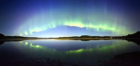 Northern lights panorama with reflection on the lake at night. Stock Photo