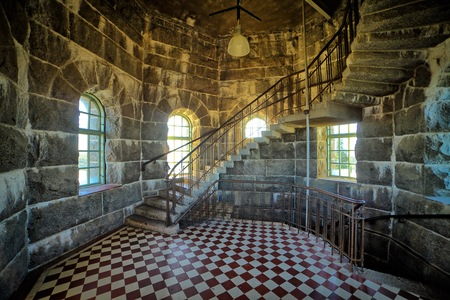 Old tower interior with curved staircase, HDR image.