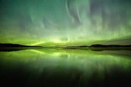 polar lights: Northern lights Aurora Borealis above a lake with still water and reflections at night. Stars on the night sky behind the polar lights.