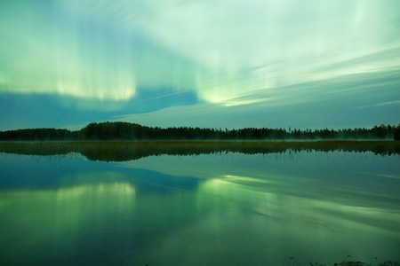 still water: Northern lights (Aurora Borealis) glowing in the night sky over a beautiful lake in Finland. Vibrant colors on the sky and symmetric reflections on the still water of the lake.