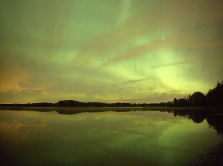 still water: Northern lights Aurora Borealis in the night sky over a beautiful lake in Finland. Vibrant green colors on the sky and reflections on the still water of the lake.