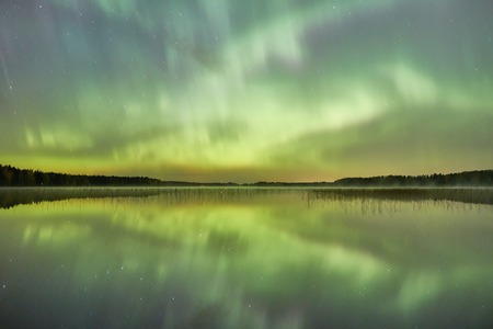 still water: Northern lights Aurora Borealis glowing in the night sky over a beautiful lake in Finland. Vibrant colors on the sky and symmetric reflections on the still water of the lake.