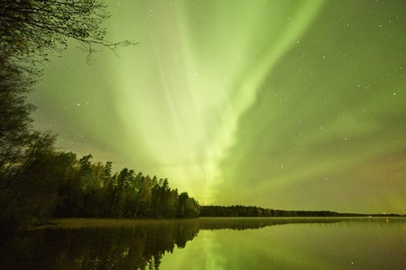 Northern lights Aurora Borealis glowing in the night sky over a beautiful lake in Finland. Vibrant colors on the sky and reflections on the still water of the lake. Stock Photo