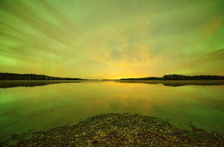 still water: Northern lights aurora borealis in the night sky over beautiful lake. Green color on the sky and reflections on still water of the lake. HDR image.