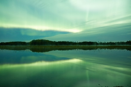 still water: Green northern lights Aurora Borealis glowing in the night sky over a beautiful lake in Finland. Vibrant colors on the sky and symmetric reflections on the still water of the lake. Stock Photo