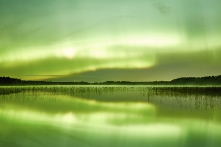 still water: Northern lights Aurora Borealis in the night sky over a beautiful lake in Finland. Vibrant colors on the sky and symmetric reflections on the still water of the lake.