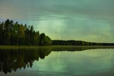 still water: Green glowing northern lights Aurora Borealis in the night sky over a beautiful lake in Finland.  Surreal landscape with vibrant colors on the sky and reflections on the still water of the lake.