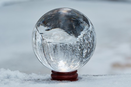 Winter scene with a transparent crystal ball reflecting the snowy landscape. Icy river appearing upside down on the ball.