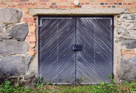 barn doors: Rustic barn doors and old countryside building exterior. Stone wall constructed with concrete and bricks.