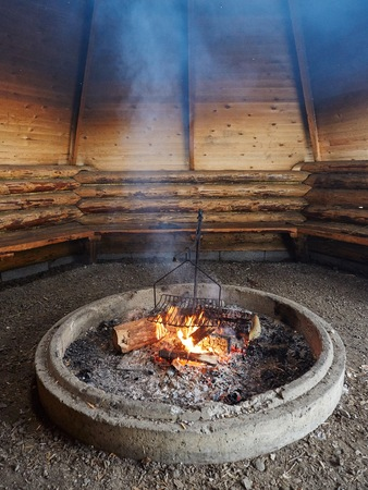 fire place: Smoke rising from outdoor fire place in a barbecue hut.