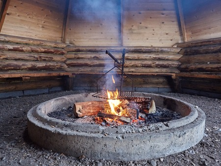 the place is outdoor: Smoke rising from outdoor fire place in a barbecue hut.