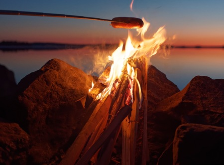 atmospheric: Sausage grilled on the campfire at sunset. Still water of the lake on the background with atmospheric evening light. Stock Photo