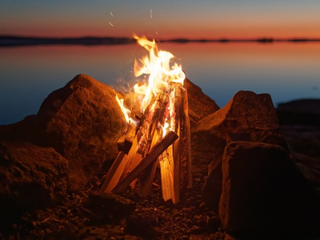 atmospheric: Fire and flames of atmospheric campfire on the beach at night. Still water of the lake on the backgound with warm colors of sunset. Very shallow dept of field. Stock Photo