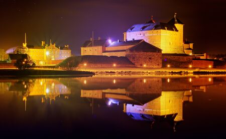 Night scene and medieval castle by the lake in Finland. Reflection of the castle n the still water of the lake. Editorial