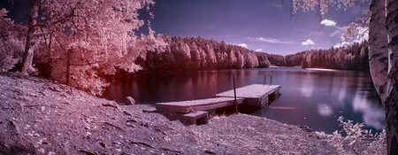 Fantasy lake landscape panorama taken with infrared filter. Ethereal atmosphere of the lake scene created using surreal colors.