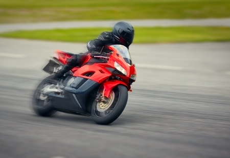 cornering: Fast motorbike racing on the race track at high speed. Composite image with heavy image editing.