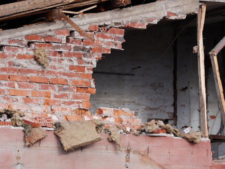 Hole in the brick wall of wrecked building at demolition site.