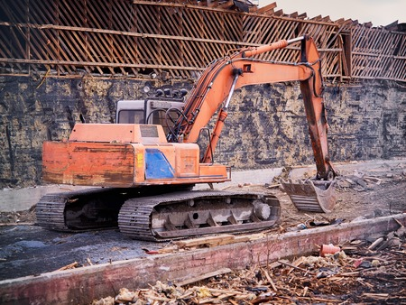 Excavator at demolition site breaking down the building.