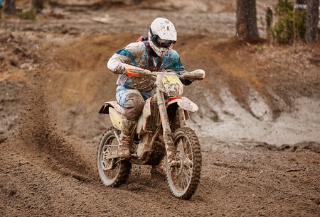 Motocross driver in action accelerating the motorbike  on muddy race track. Stock Photo