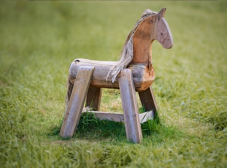 Wooden horse in the middle of grass in summer.