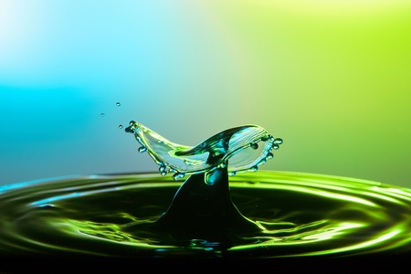 Water drop collision close up image with a green and blue background. Stock Photo