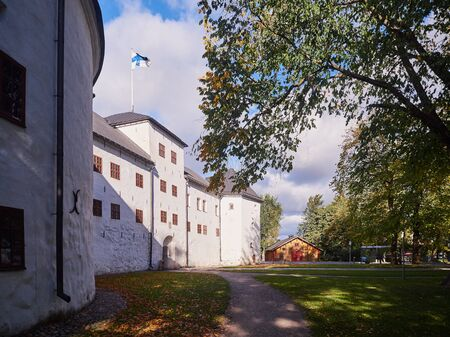 Turku castle in bright sunshine in Finland with the finnish flag on a sunny summer day. Editorial
