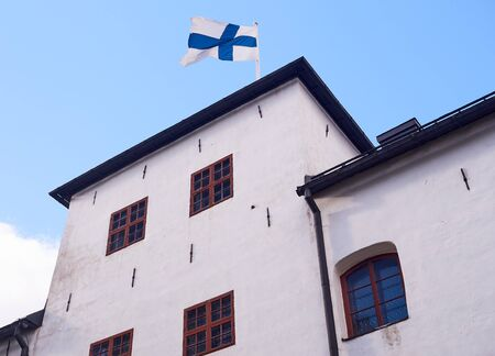 Finnish flag on the roof of the Turku castle in Finland in bright sunshine.