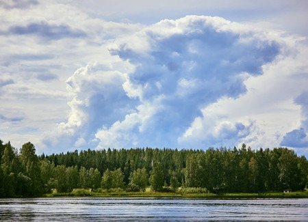 Majestic thunder clouds forming in the bright summer day sky in Finland. Stock Photo - 76839878