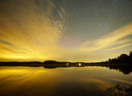 Stars and sunset in Finland. Reflection of the forest skyline in the calm water of a lake. Stock Photo