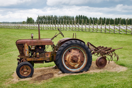 Rusty old tractor standing unused on the field.
