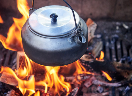 Metallic coffee pot in campfire heat. Wood burning with flames beneath the pot. Stock Photo