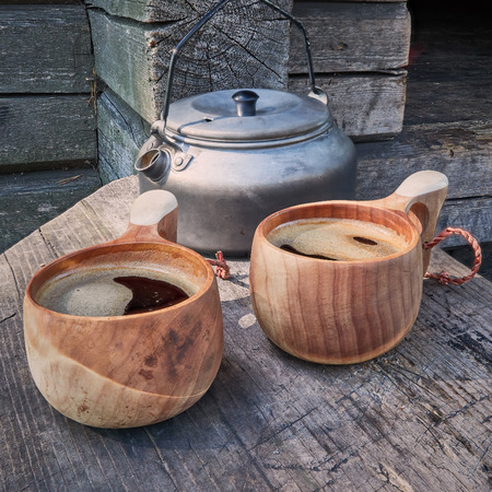 Two wooden mugs filled with hot fresh coffee on the campsite while trekking. Stock Photo