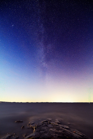 The Milky Way and stars in peaceful lake scene at night. Some light pollution and city lights on the horizon. Vertical image.