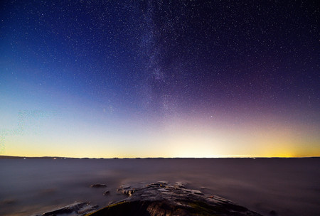 The Milky Way and stars in peaceful lake scene at night. Some light pollution and city lights on the horizon Stock Photo