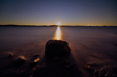 Moon shining just above the horizon at night. Big stone on still water of peaceful lake in Finland.