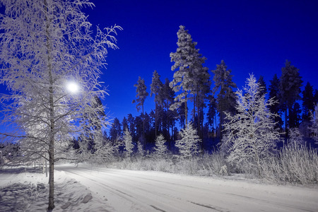A road through peaceful winter night scene under beautiful blue sky. Snow cowered trees in very cold weather in Finland.
