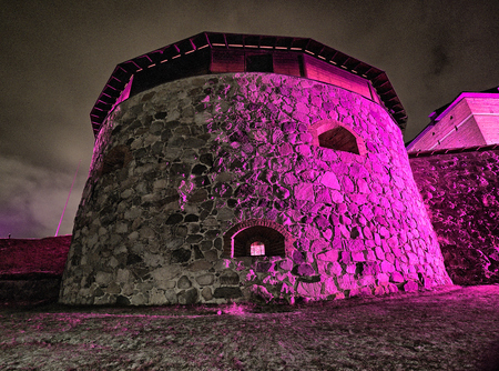Medieval castle exterior night scene during light festival. Surreal view with very colorful and vibrant illumination.
