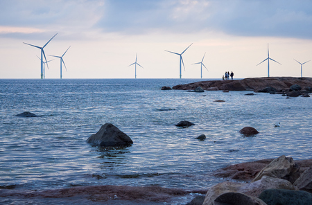 People watching wind mill power generator farm for renewable energy production along coast of Bothnian Sea near Pori, Finland. Alternative green clean energy, ecology.