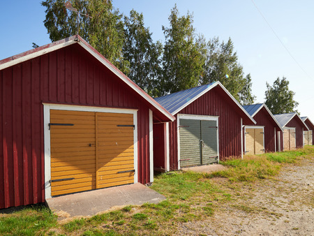 Beautiful small boathouses or cottages in a row in small port of Svedjehamns, Finland. Warm weather on a sunny summer day.