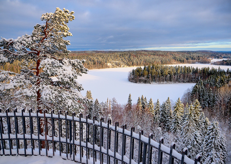 National landscape view at Aulanko nature park in Hämeenlinna, Finland. Icy lake and snowy forest on a sunny winter day. The sun is shining to the frozen trees on the foreground. Stock Photo