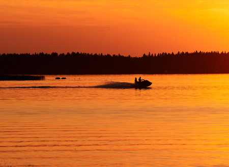 A jet-ski driving in calm sea water in Vaasa, Finland.  Sunset sky and colorful waves in the water.  activity, hobby and leisure time consept.