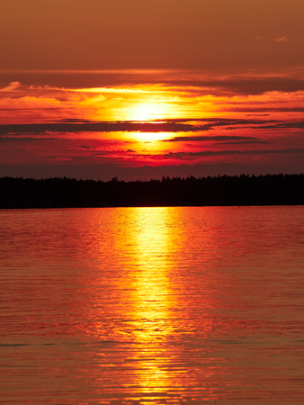 Red sunset sky with the sun and colorful clouds above calm sea water in Vaasa, Finland. The bright disk of the sun is partly hidden by the clouds. Very dramatic sky. Vertical image. Stock Photo