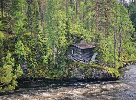Old fishermans hut along the Oulankajoki river at the Oulanka National Park in Kuusamo, Finland. Scenic view of the northern nature and the flowing water in the stream. Stock Photo