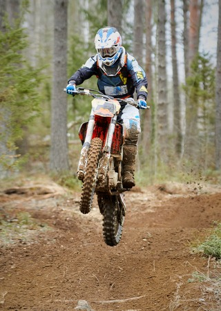Motocross driver jumping with the bike at high speed on the race track. Stok Fotoğraf