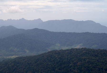 Amazing landscape view from the observation tower at Gunung Raya, the highest point in Langkawi, Malaysia. Distant mountains in the mist and the ocean on the background. Tranquility and serenity.