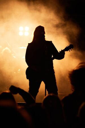 A heavy metal star playing guitar. Hard rock guitarist in concert.
