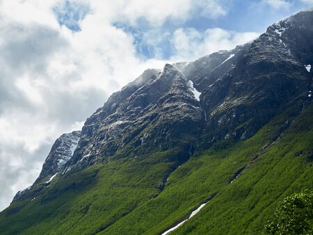 Closeup on snow covered fjords of Norway with ice and snow on the steep mountain edges. Clouds hanging low on the mountain peaks.