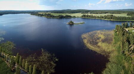 Aerial view of blue lake and green forests on a sunny summer day. Birds eye view drone photography. Ruovesi, Finland.