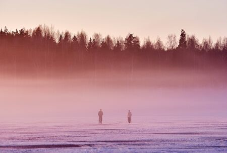 Dramatic sunset with two skiers on foggy ice of frozen lake in Finland in winter.